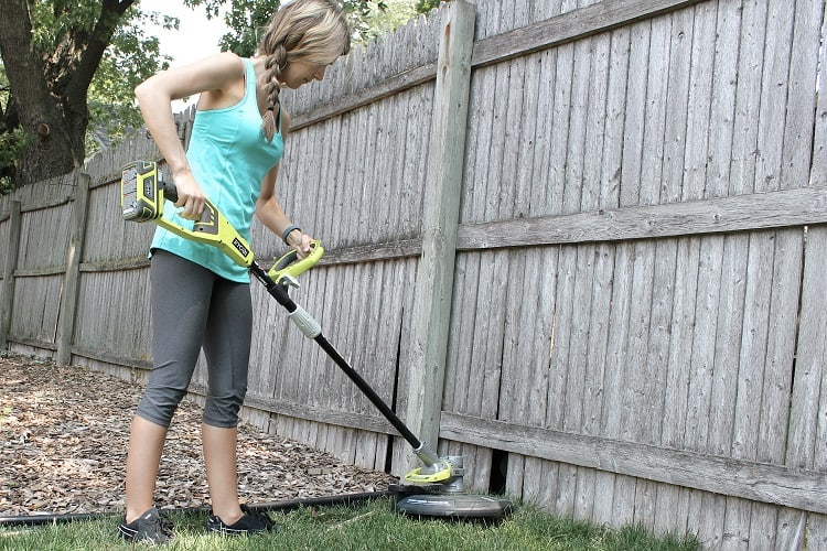 Woman Using Cordless String Trimmer