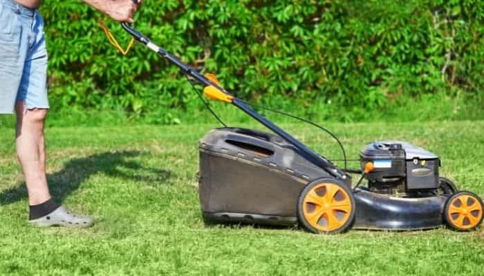 lawn mower blade is being held by a man